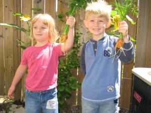 Kenton and Maya gather their carrot harvest